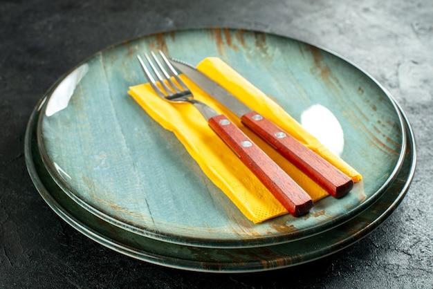 Gelbes serviettenmesser und gabel von unten auf runden tellern auf schwarzem tisch