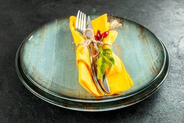 Gelbes serviettenmesser und gabel von unten mit seil auf tellern auf schwarzem tisch gebunden
