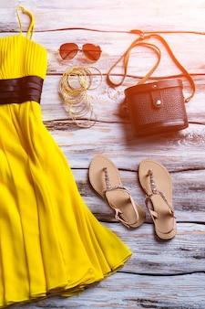 Gelbes sommerkleid und sandalen. beige sandalen, geldbörse und kleid. nagelneue kleidung für mädchen. beste preise für neuware.
