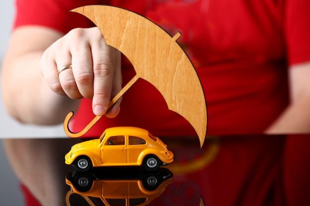 Gelbes spielzeugauto der männlichen armabdeckung