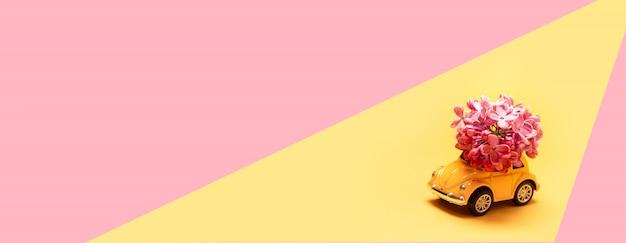 Gelbes spielzeugauto liefert einen blumenstrauß von flieder auf rosa gelb