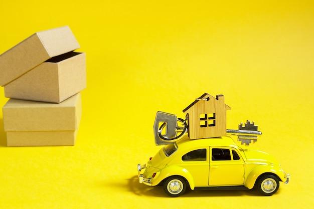 Gelbes spielzeugauto mit einem schlüssel zum haus auf dem dach auf einem beleuchtenden hintergrund und verpackungskästen.