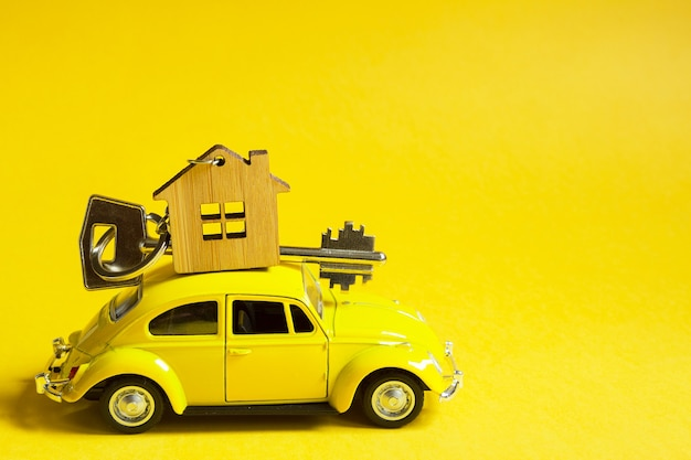Gelbes spielzeugauto mit einem schlüssel zum haus auf dem dach auf einem farbhintergrund.