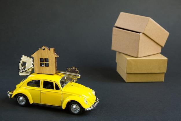 Gelbes spielzeugauto mit einem schlüssel zum haus auf dem dach auf einem schwarzen hintergrund.