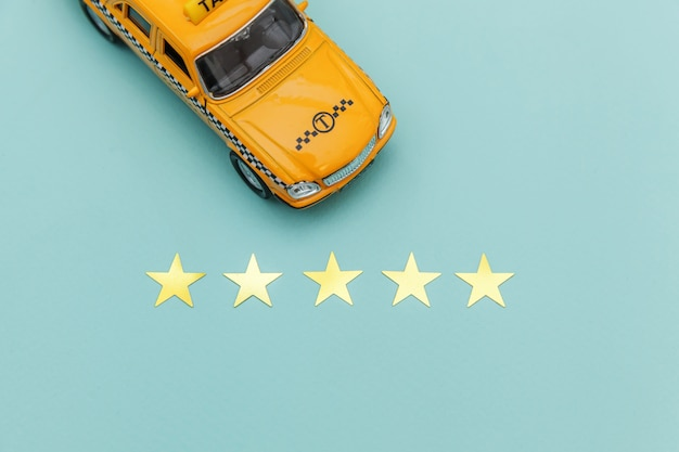 Gelbes spielzeugauto taxi und bewertung mit 5 sternen lokalisiert auf blauem hintergrund. telefonische anwendung von taxi service für online suche telefonieren und buchung cab concept. taxi-symbol. kopieren sie platz.