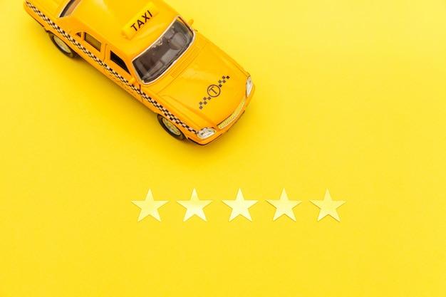 Gelbes spielzeugauto taxi und bewertung mit 5 sternen lokalisiert auf gelbem hintergrund. telefonische anwendung von taxi service für online suche telefonieren und buchung cab concept. taxi-symbol. kopieren sie platz.