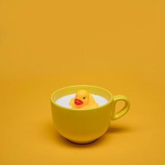 Gelbes stillleben der badeente in der tasse milch