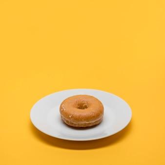 Gelbes stillleben des donuts auf platte