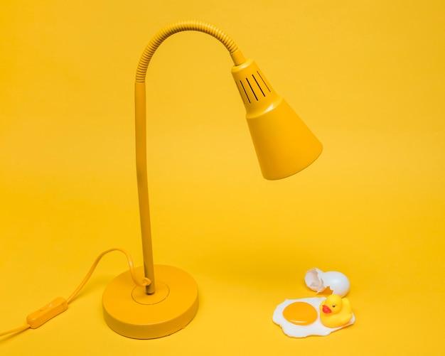 Gelbes stillleben des eies unter lampe