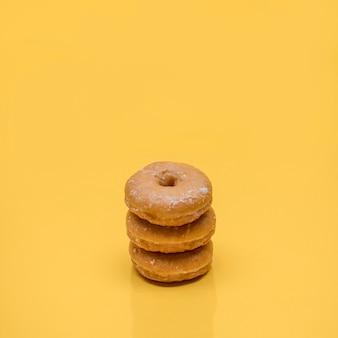 Gelbes stillleben von drei donuts