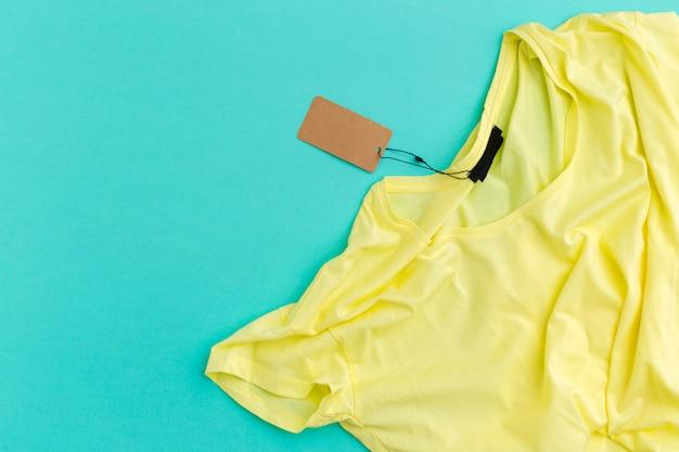 Gelbes t-shirt mit draufsicht des leeren aufklebertags
