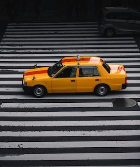 Gelbes taxi auf einem zebrastreifen in japan