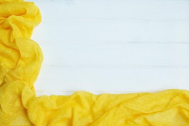 Gelbes textil der tischdecke auf weißem hölzernem hintergrund. frühling oder ostern hintergrund