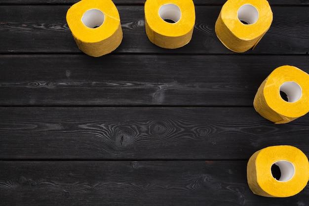Gelbes toilettenpapier auf draufsicht des schwarzen hölzernen hintergrundes