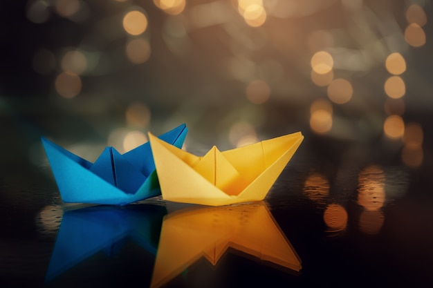 Gelbes und blaues papierschiff versendet auf dunkelheit