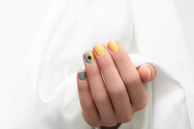 Gelbes und graues nageldesign. gepflegte weibliche hand auf weißem stoffhintergrund.