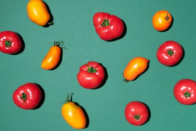 Gelbes und rotes tomatenmuster auf grünem hintergrund