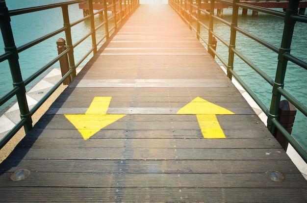 Gelbes verkehrspfeilzeichen in zwei richtungen, das auf richtung zwei auf holzbrücke zeigt