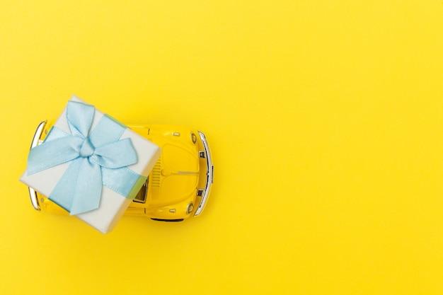 Gelbes vintage retro spielzeugauto, das geschenkbox auf dach lokalisiert auf gelbem tisch liefert