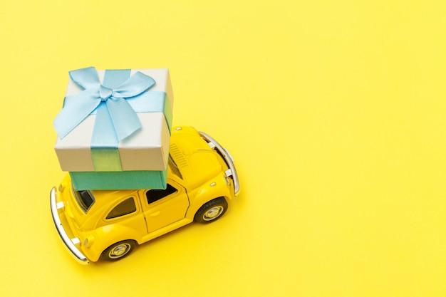 Gelbes vintage retro-spielzeugauto, das geschenkbox auf dach lokalisiert auf trendigem gelbem hintergrund liefert