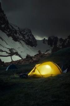 Gelbes zelt auf dem hintergrund von berggipfeln im schnee nachts