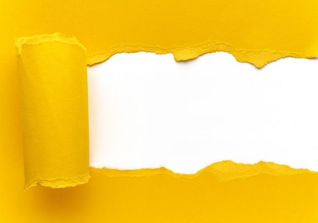 Gelbes zerrissenes papier. quadratisches loch mit weißem hintergrund.