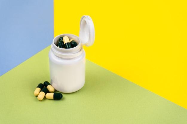 Gelbgrüne pillen in einem weißen glas auf farbigen nahrungsergänzungsmitteln multivitamine pflanzliche arzneimittel