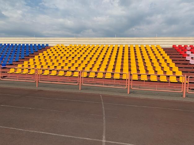 Gelbgrüne, rote und blaue sitze hintereinander im stadion ohne spieler und publikum