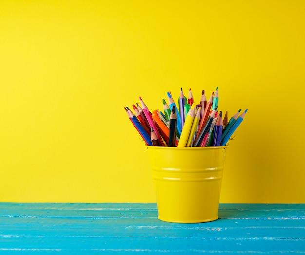 Gelbgrüneimer mit mehrfarbigen hölzernen bleistiften und stiften