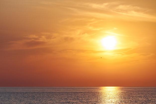 Gelborange sonnenuntergang auf meer oder ozean, strandküste