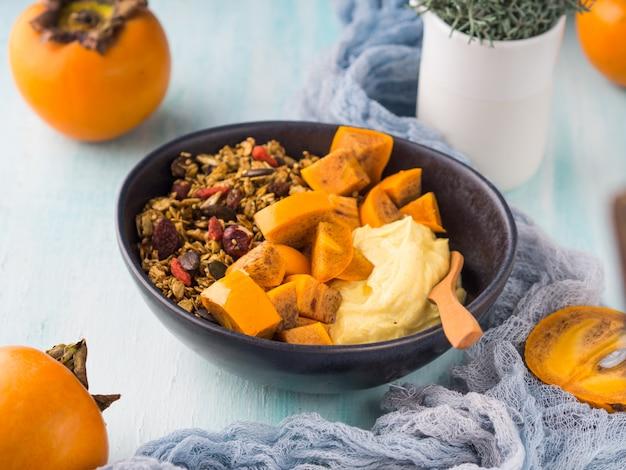 Gelbwurz-joghurtschüssel mit persimone und granola