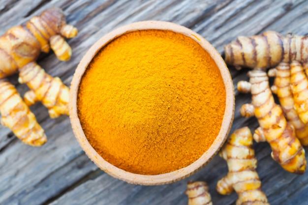Gelbwurzpulver in den schüsseln und in der frischen gelbwurz auf altem hölzernem hintergrund. kräuter