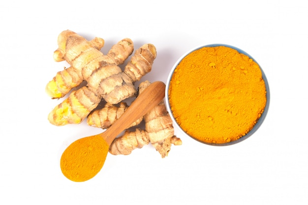 Gelbwurzpulver (kurkuma) in der braunen schüssel auf weißem hintergrund. kräuter-