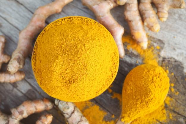 Gelbwurzpulver und frisches turemric in den hölzernen schüsseln auf holztisch. kräuter stammen aus südostasien.