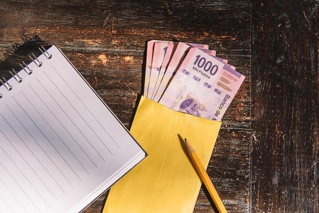 Geld - 1000 pesos rechnungen ein notizbuch und ein bleistift - banknoten, rechnungen, mexikanische pesos