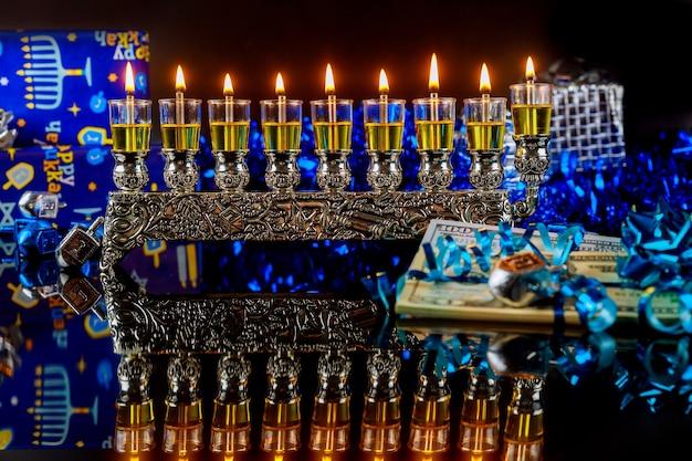 Geld als geschenk mit menora für chanukka auf schwarzem hintergrund. jüdische feiertagstradition.