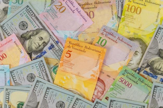 Geld amerikanische hundert-dollar-scheine serie von banknoten mit verschiedenen papierscheinwährung venezolanischer bolivar, venezuela wirtschaftskrise