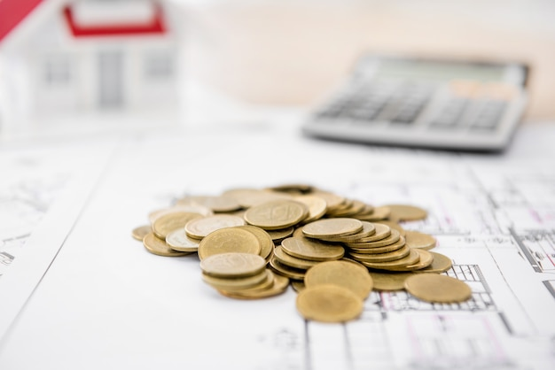 Geld auf planpapier mit unscharfem hausmodell und taschenrechner im hintergrund