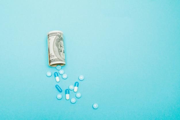 Geld aufgerollt mit pillen, die isoliert auf blau herausfließen, hohe kosten des teuren medikamentenkonzepts