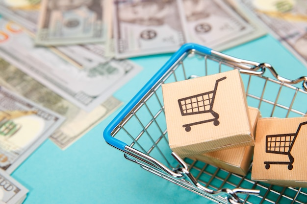 Geld banknoten dollar und einkaufskorb mit boxen auf blau