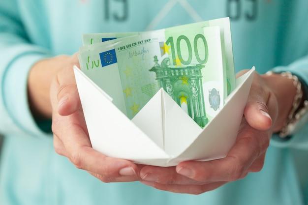 Geld banknoten und papierschiffe.