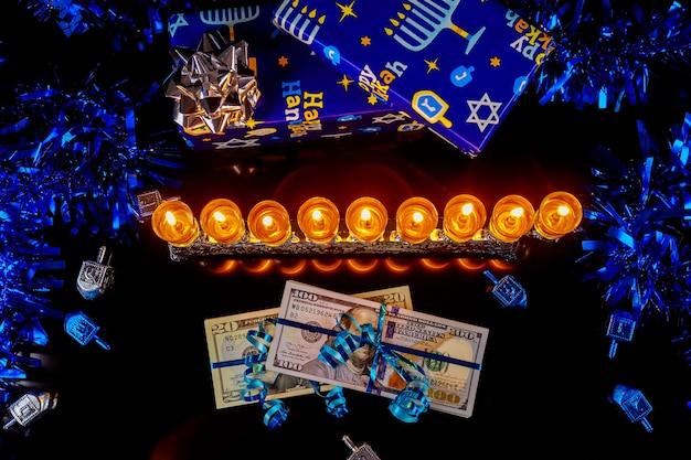 Geld bargeld als geschenk mit menora für chanukka auf schwarzem hintergrund. jüdische feiertagstradition.
