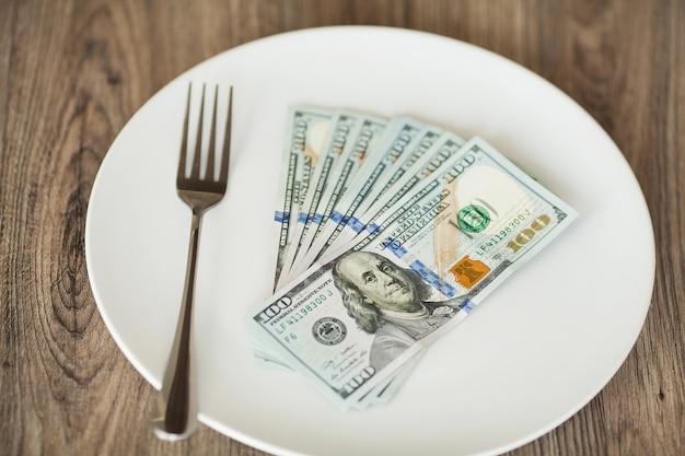 Geld, das auf der platte mit gabel liegt. dollar foto. gierige korruption. bestechungsidee
