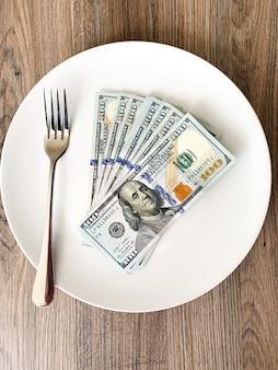Geld, das auf der platte mit gabel liegt. dollar foto. gieriges korruptionskonzept. bestechungsidee