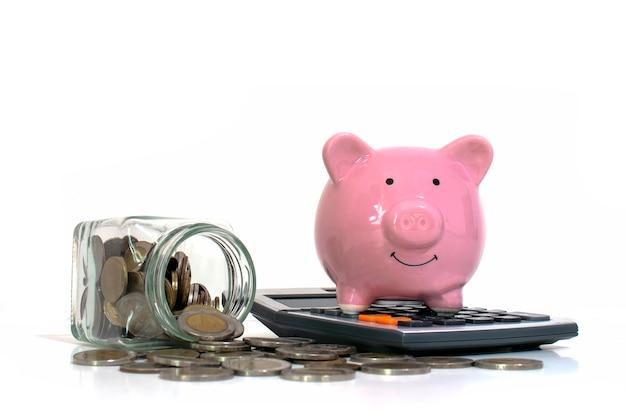 Geld, das aus einem geldkrug wie ein sparschwein auf einem taschenrechner auf einem weißen hintergrundkonzept des ausgebens und des sparens geld fließt.