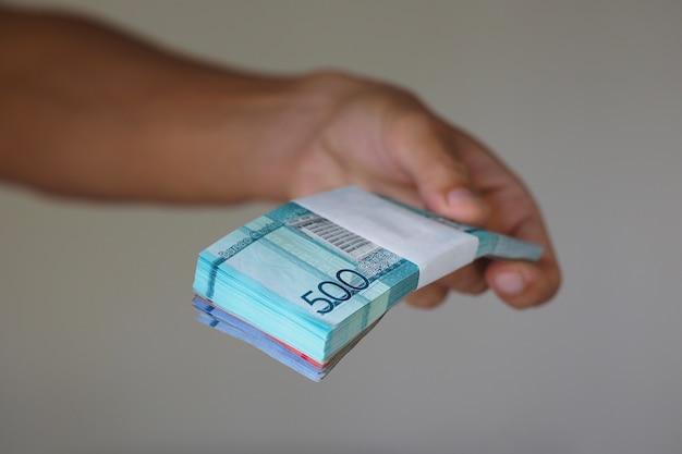 Geld der dominikanischen republik in der hand einer banknote von 500 pesos.