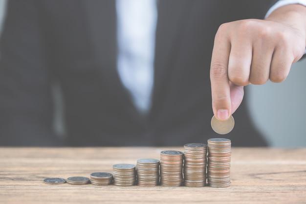 Geld des münzenstapels steigern wachsendes wachstum mit vorbildlichem weißem haus auf holztisch.