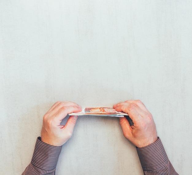 Geld des russischen rubels in den mannhänden, draufsicht über einen grauen hintergrund mit raum für text