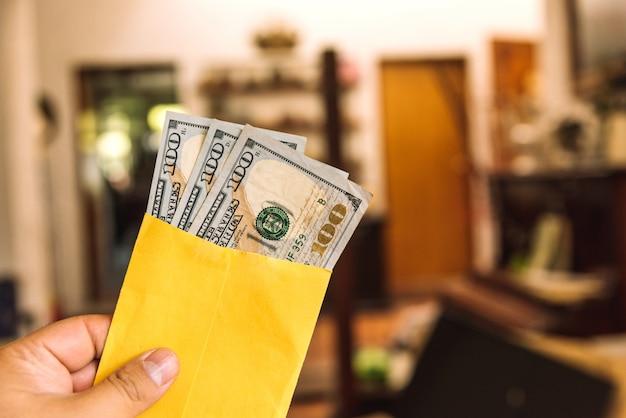 Geld - eine hand, die einen umschlag mit 100-dollar-scheinen hält
