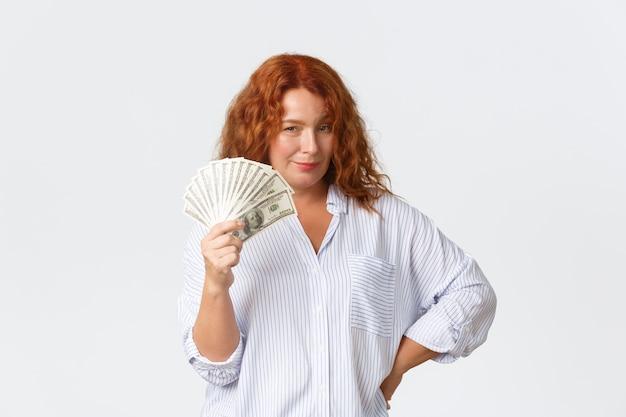 Geld-, finanz- und personenkonzept. freche und freche lächelnde rothaarige frau mittleren alters, die mit viel geld ein angebot macht, dollars zeigt und mit ihrem einkommen prahlt, weiße wand